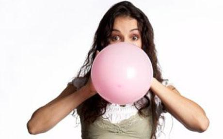 Mid adult woman blowing pink balloon, portrait